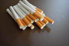 Molte sigarette su un fondo opaco marrone immagine stock