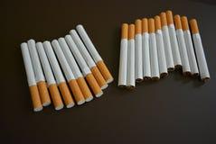 Molte sigarette su un fondo opaco marrone immagini stock