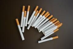 Molte sigarette su un fondo opaco marrone fotografia stock