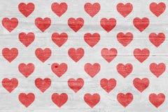 Molte siluette rosse del cuore su una plancia di legno Fotografie Stock