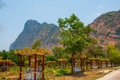 Molte statue del Buddhas che si siedono, in mezzo di bello paesaggio con le montagne nel giorno soleggiato Hpa-An, Myanmar burma fotografia stock libera da diritti