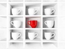 Molte tazze di bianco e una tazza rossa sullo scaffale, Immagini Stock