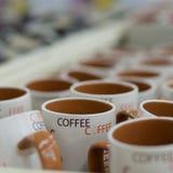 Molte tazze di caffè macchiato in una riga da vendere Fotografia Stock Libera da Diritti