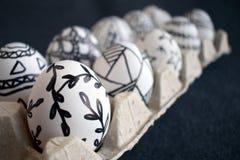 Molte uova di Pasqua con i modelli grafici di scarabocchio in imballaggio del cartone Immagine Stock