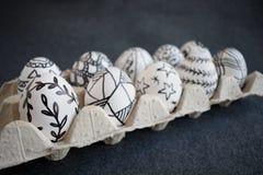 Molte uova di Pasqua con i modelli grafici di scarabocchio in imballaggio del cartone Immagini Stock Libere da Diritti