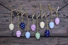 Molte uova di Pasqua variopinte che appendono sulla linea Immagine Stock