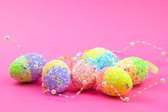 Molte uova di Pasqua variopinte su un fondo rosa Posto per testo fotografie stock libere da diritti