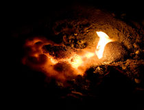 Molten lava. Close-up image of glowing molten lava and a flame next to it royalty free stock images