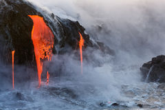 Molten Lava dripping into the ocean Stock Image
