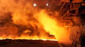 Molten metal flowing in chute at the factory surrounded by steam clubs. Stock footage. Heavy industry and metallurgical. Molten metal flowing in chute at the stock photos
