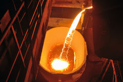 Molten metal poured from ladle. For casting Stock Image