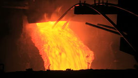 Molten metal pouring out of furnace. Liquid metal from blast furnace