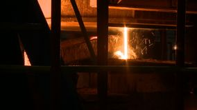 Molten metal pouring out of furnace. Liquid metal from blast furnace stock footage
