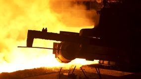 Molten metal pouring from the special mechanism, metallurgy concept. Molten steel flowing in metallurgical chute behind stock footage