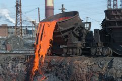 The molten steel is poured into the slag dump. The molten slag is poured from a bucket mounted on a railway platform Stock Photos