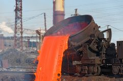 The molten steel is poured into the slag dump. The molten slag is poured from a bucket mounted on a railway platform Stock Images