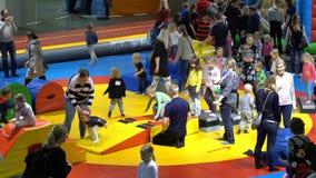 Molti bambini e genitori nel campo da giuoco al deposito Lasso di tempo archivi video