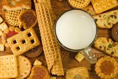 molti biscotti deliziosi e latte sul primo piano della tavola fotografie stock