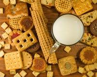 molti biscotti deliziosi e latte sul primo piano della tavola immagini stock