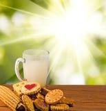 molti biscotti deliziosi e latte sul primo piano della tavola immagine stock