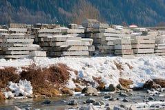 Molti blocchi impilati di granito ruvido in una cava fotografia stock