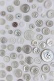 Molti bottoni di cucito ordinati su fondo bianco Fotografie Stock