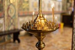 Molti candele brucianti della cera nella chiesa ortodossa fotografie stock libere da diritti