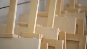 Molti cavalletti di legno sta la parete vicina nello studio di arte video d archivio