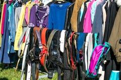 Molti cinghie e abbigliamento adulto sullo scaffale alla vendita di garage Immagine Stock