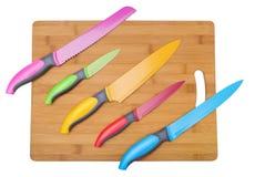Molti coltelli colorati originale Su un bordo di legno per tagliare Fotografia Stock Libera da Diritti