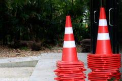 Molti coni di traffico sul pavimento del cemento davanti alla costruzione immagini stock libere da diritti