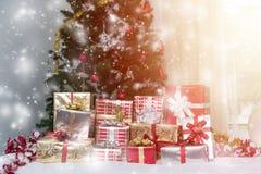 Molti contenitori di regalo dei regali di Natale su una tavola con il tre di Natale fotografia stock