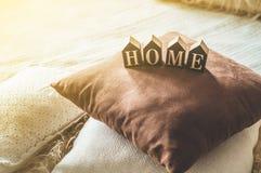 Molti cuscini accoglienti decorativi e la CASA dell'iscrizione immagini stock