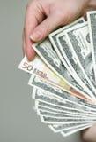 Molti dollari che cadono sulla mano dell'uomo con soldi Fotografie Stock Libere da Diritti