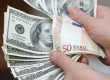 Molti dollari che cadono sulla mano dell'uomo con soldi, isolati Fotografia Stock