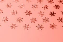Molti fiocchi di neve luccicanti su un fondo di corallo fotografie stock