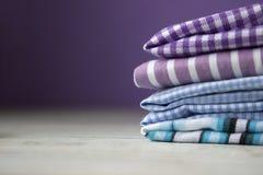 Molti generi di tessuti di cotone in bande e di gabbia su un fondo lilla immagine stock