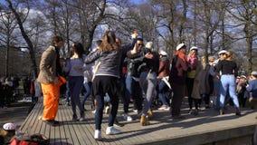 Molti giovani felici che ballano latino ardente nel parco della città stock footage
