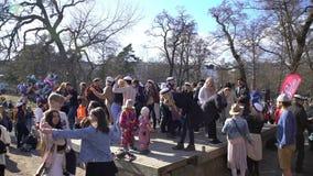 Molti giovani felici che ballano latino ardente nel parco della città archivi video