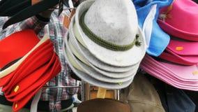 Molti hanno ritenuto cappelli colorati multi e differenti per appendere su un gancio della via al stock footage
