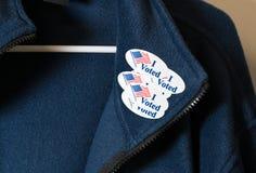 Molti ho votato gli autoadesivi sulla giacca blu appesa sul gancio fotografie stock