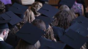 Molti laureati che indossano i cappucci accademici, fondo di statistiche di istruzione superiore video d archivio