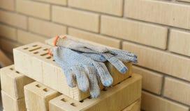 Molti mattoni e guanti sono pronti ad essere usato per lavoro Immagini Stock Libere da Diritti