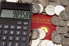 Molti monete e calcolatore sui precedenti di accumulazione dell'alloggio costituiscono un fondo per il libretto bancario Fotografia Stock