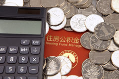 Molti monete e calcolatore sui precedenti di accumulazione dell'alloggio costituiscono un fondo per il libretto bancario Immagine Stock Libera da Diritti