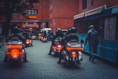 Molti motociclisti guidano i motocicli alla notte nella vista della città da dietro, una luce notturna calda libertà del moviment fotografia stock libera da diritti