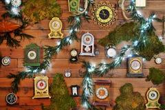 Molti orologi dell'annata sulla parete di legno con la decorazione del ` s del nuovo anno immagine stock