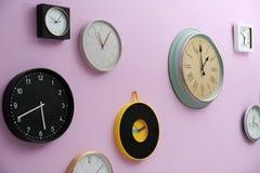 Molti orologi differenti che appendono sulla parete di colore fotografia stock libera da diritti