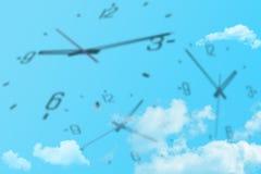 Molti orologi in vario tempo che vola in cielo blu immagini stock libere da diritti