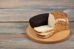 Molti pane e panini misti di pane al forno sul fondo di legno della tavola Immagine Stock
